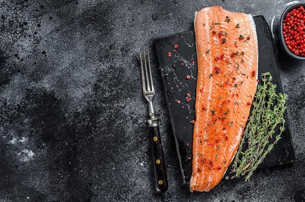Филе морской рыбы из лосося или форели с солью и розовым перцем. черный деревянный фон. вид сверху. скопируйте пространство.
