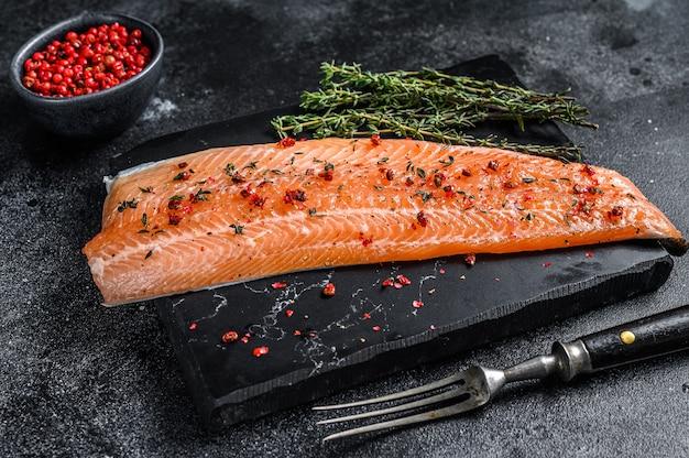 Филе морской рыбы из лосося или форели с солью и розовым перцем. черный деревянный фон. вид сверху.