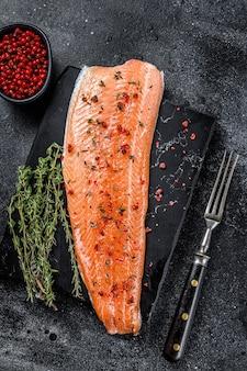 Филе морской рыбы из лосося или форели с солью и розовым перцем. черный деревянный стол. вид сверху.