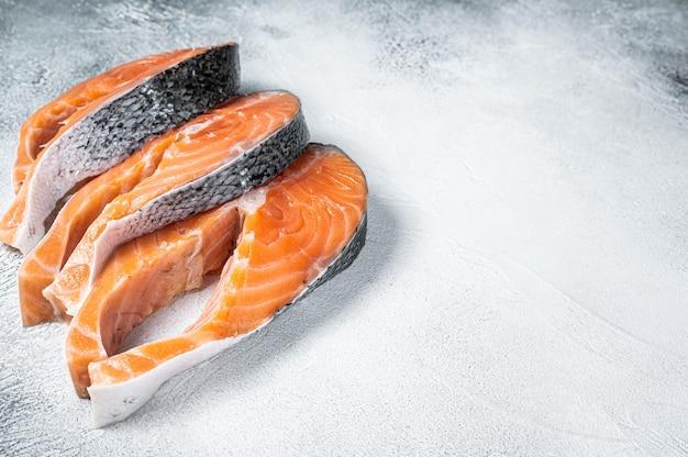 Стейки из лосося или форели, сырая рыба, приготовленная для приготовления. белый фон. вид сверху. скопируйте пространство.