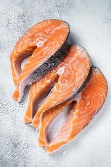 Стейки из лосося или форели, сырая рыба, приготовленная для приготовления. белый фон. вид сверху.