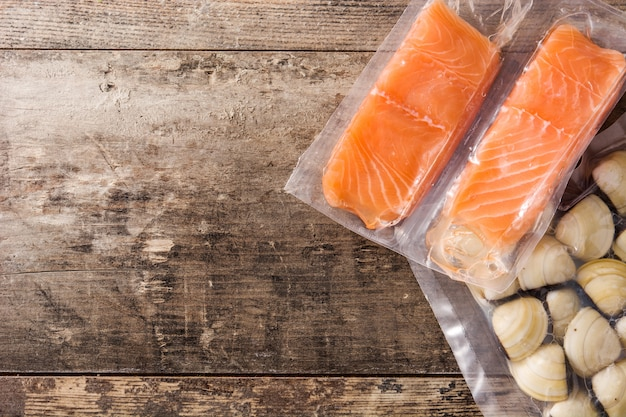 Salmon packaged in plastic on wooden table, top view, copy space