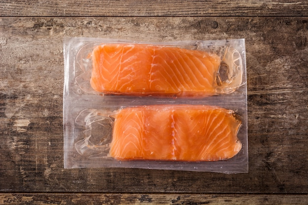 Salmon packaged in plastic on wooden table