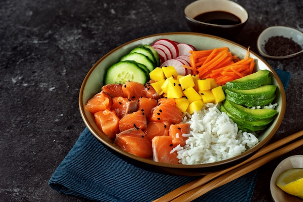 Salmon poke bowl with avocado, rice, carrot and cucmber