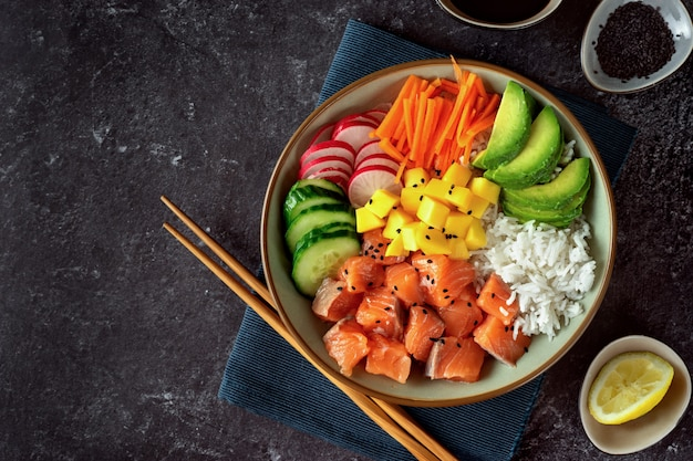 Salmon poke bowl with avocado, rice, pickled carrots and cucumber
