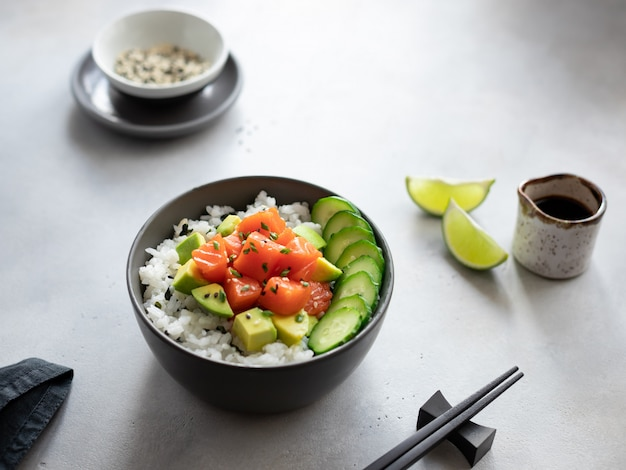 Salmon poke bowl with rice, avocado, cucumber and soy sauce on a gray concrete background. traditional hawaiian raw fish salad.
