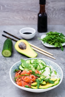 Salmon poke with avocado, arugula and cucumber in a bowl