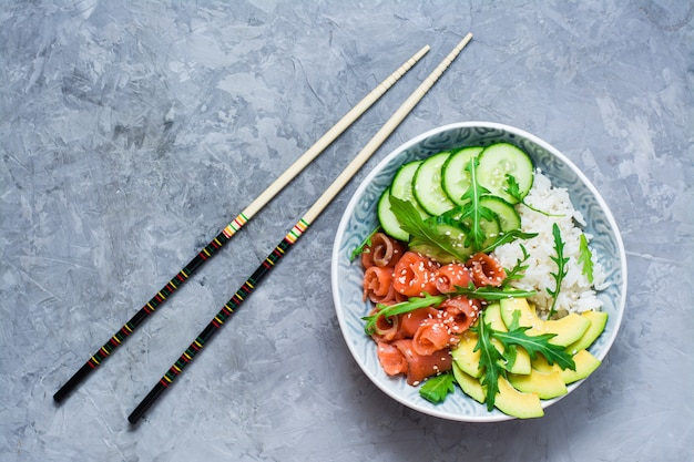 Salmon poke with avocado and cucumber in a bowl and chopsticks