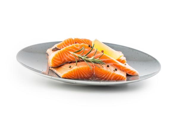 연어. 흰색 바탕에 생 연어 스테이크 허브 후추 레몬. 프리미엄 사진