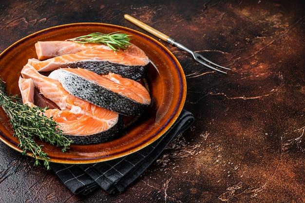 Сырые стейки лосося на деревенской тарелке с травами. темный фон. вид сверху. скопируйте пространство.