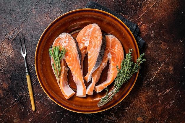 Сырые стейки лосося на деревенской тарелке с травами. темный фон. вид сверху.