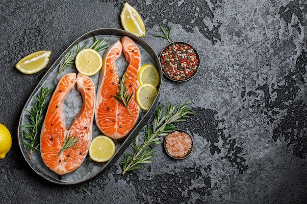 Лосось. стейк из сырой форели из красной рыбы с ингредиентами для приготовления. приготовление лосося, морепродуктов. концепция здорового питания