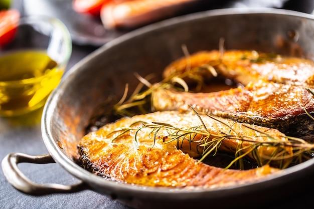 Жареные стейки из лосося, розмарина, салата, перца, оливкового масла - крупный план.