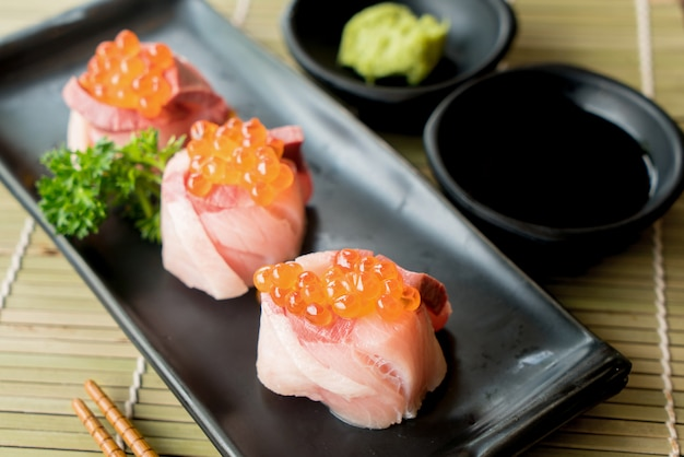 Salmon roe on hamachi sushi on black plate along with japanese sauce and green leaf decoration.