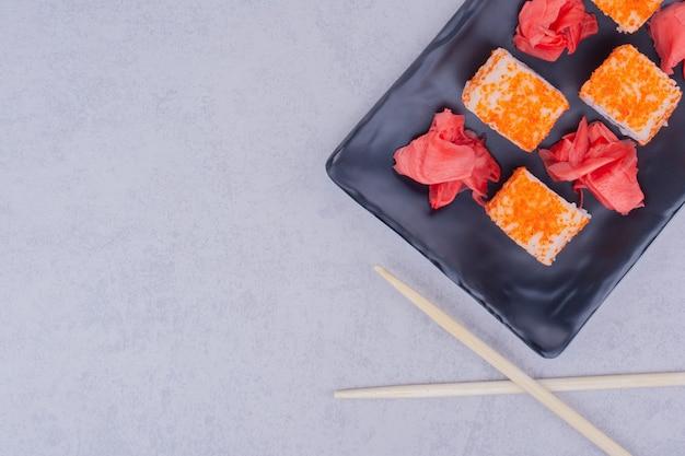 검은 접시에 연어 롤과 빨간 절인 생강.