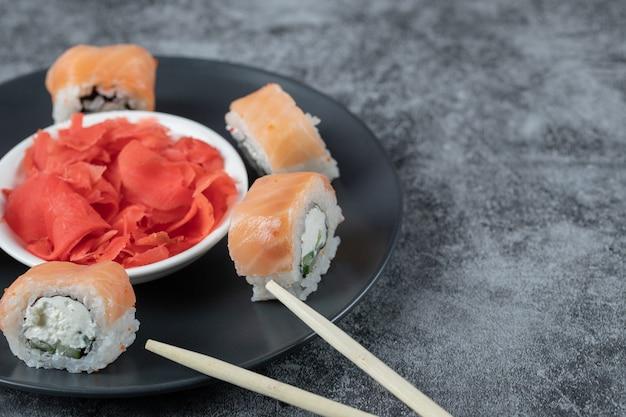 Involtini di salmone in un piatto nero con zenzero rosso marinato.