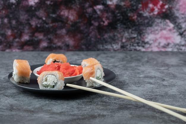 Рулетики из лосося в черном блюде с маринованным красным имбирем.