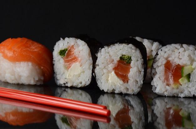 鮭巻きまたは巻き寿司。握り寿司、黒地に反射あり