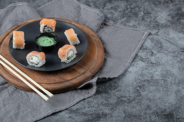 Salmon rolls with cream cheese in a black plate with wasabi sauce.
