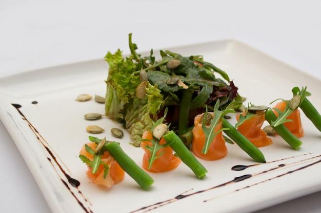 Salmon salad, pumpkin seeds and asparagus on a plate