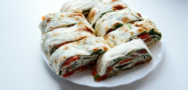 하얀 접시에 연어 샐러드 샌드위치입니다. 붉은 생선과 양상추를 곁들인 롤 lavash 샌드위치. 얇은 아르메니아 lavash 또는 lavash. 간식.