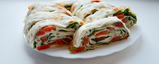 白い皿にサーモンサラダサンドイッチ。赤い魚とレタスでラヴァッシュサンドイッチを転がします。薄いアルメニアのラヴァッシュまたはラヴァッシュ。スナック。