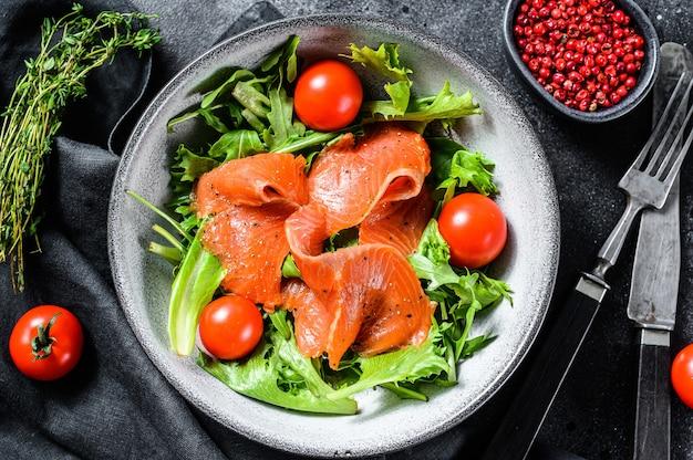 Salmon salad with arugula, cherry tomatoes and corn salad.