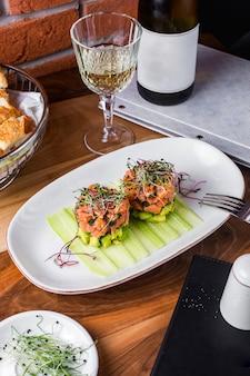 Салат из лосося с авокадо, подается с ломтиками огурца и зеленью 1