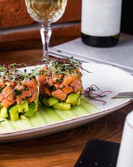 Салат из лосося с авокадо, подается с ломтиками огурца и зеленью