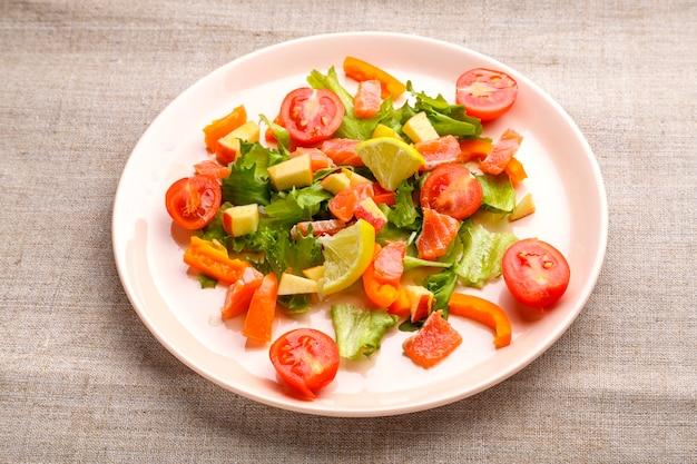 Салат из лосося с помидорами черри и зеленым салатом в тарелке из серой скатерти