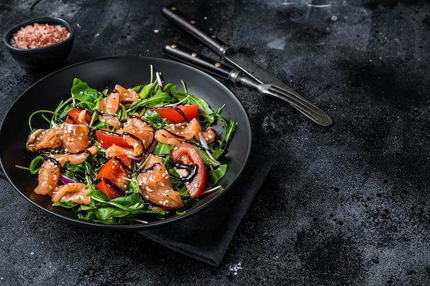 Салат из лосося с кусочками рыбы, рукколой, помидорами и зелеными овощами. черный фон. вид сверху. скопируйте пространство.