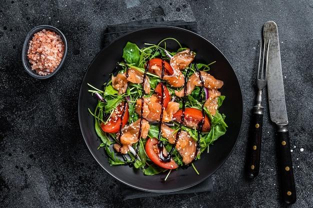 Салат из лосося с кусочками рыбы, рукколой, помидорами и зелеными овощами. черный стол. вид сверху.