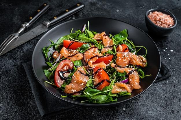 Салат из лосося с кусочками рыбы, рукколой, помидорами и зелеными овощами