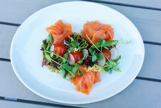 Salmon salad with mixed vegetable on white plate