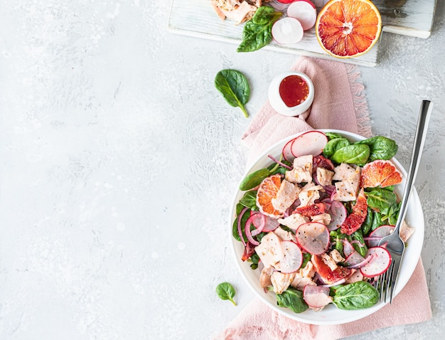 Salmon salad with orange spinach and radish with ingredient for making salad healthy food