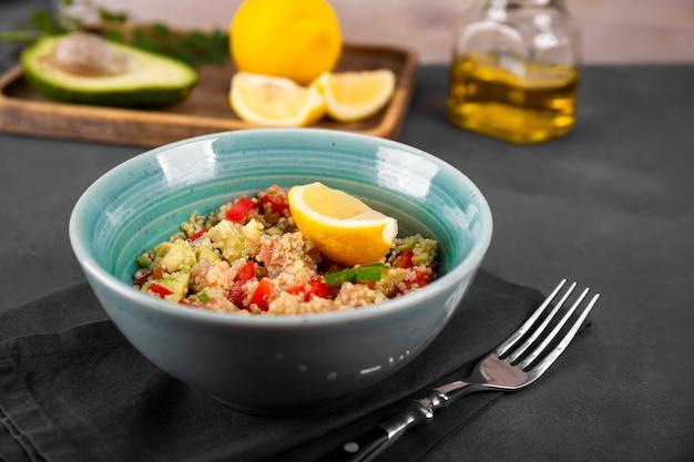 濃い灰色のテーブルの上の青いボウルにトマト、アボカド、キヌアを入れたサーモン サラダ、バランスの取れた食事の料理。