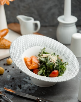 Salmon salad with vegetables in the plate