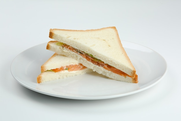하얀 접시에 구운 빵을 곁들인 연어 샌드위치. 연어 클럽 샌드위치