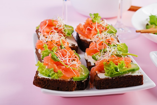 Salmon sandwiches with cream cheese and microgreen. canape with salmon.
