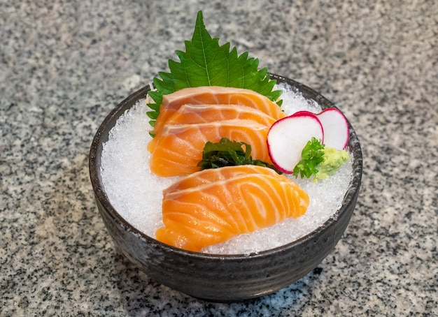 Salmon sashimi on ice in black bowl japanese food