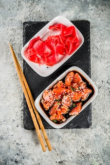 Salmon sashimi in marinade  topped with black and white sesame seeds