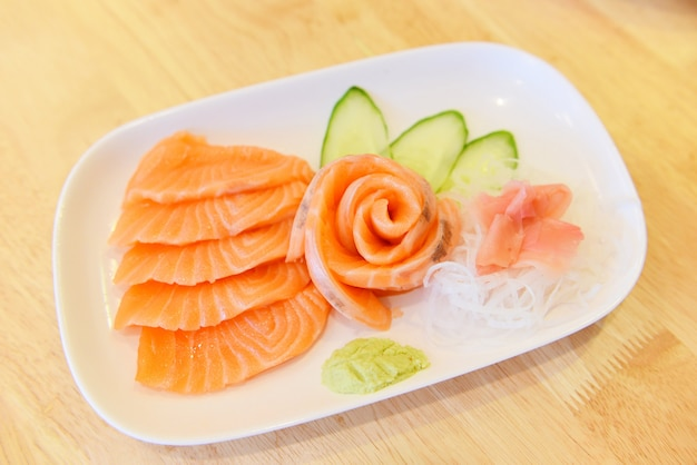 Salmon sashimi menu set japanese cuisine fresh ingredients on plate - japanese food raw sashimi salmon fillet with vegetable cucumber and wasabi in the restaurant