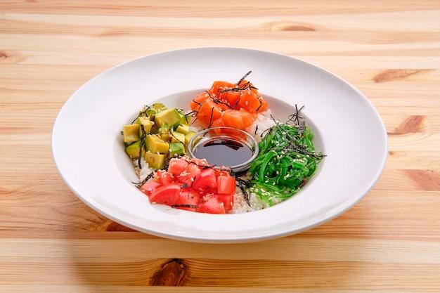 Salmon sashimi rice bowl with avocado, seawed, tomato and soy sauce