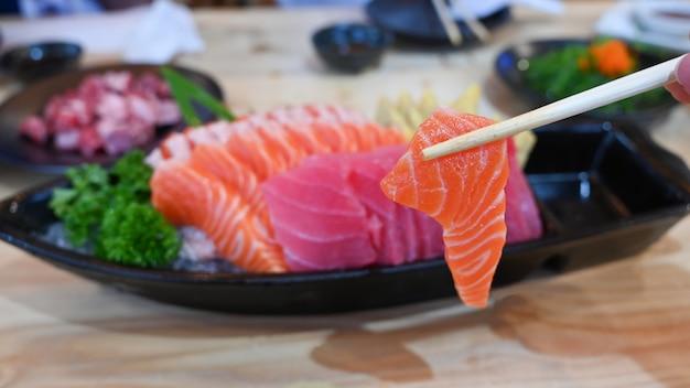 Salmon sashimi slice on chopsticks.