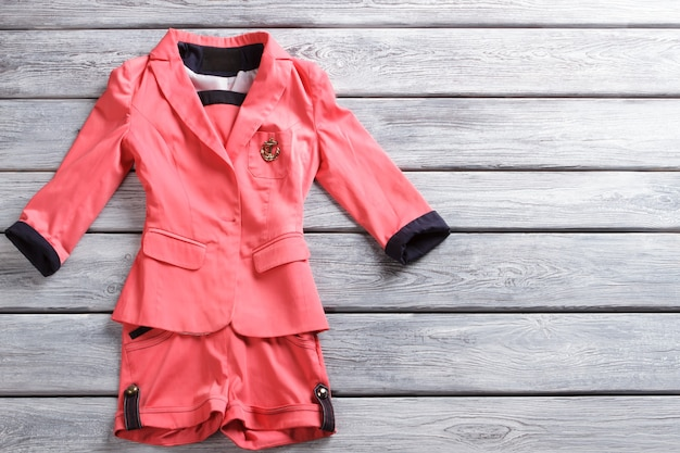 연어 짧은 슈트. 나무 배경에 짧은 양복. 봄을 위한 여성 디자이너 의류. 고품질의 독점 의류.