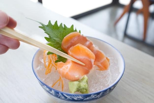 Ломтик лосося или сашими из лосося по-японски свежая подача на льду со свежим васаби