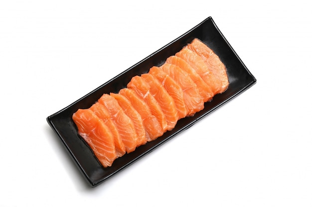 Salmon slices in black plate on white background