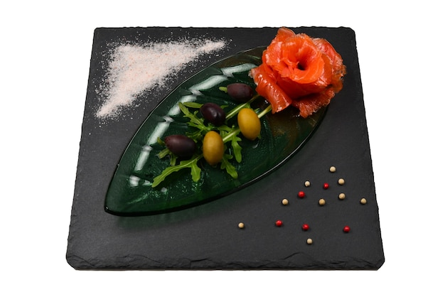 Ломтики лосося на тарелке с солью и оливками, изолированные на белом.