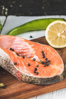 Salmon slices with black pepper balls and lemon on a wooden board
