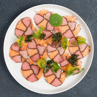 Salmon and smoked tuna carpaccio decorated with seaweed. the view from the top